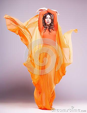 Beautiful woman in long orange dress posing dramatic in the studio
