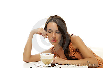 Beautiful woman looking at the cappuccino coffee i