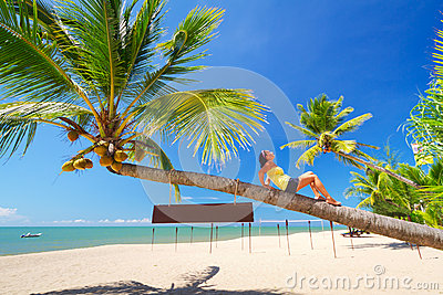 Beautiful woman lying on the amazing palm tree