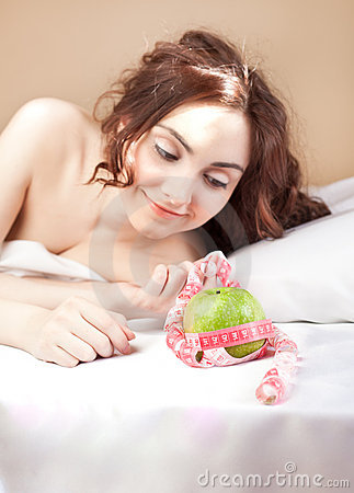Beautiful woman lying in bed with green apple