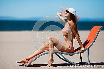 Beautiful woman lying on a deckchair at the beach