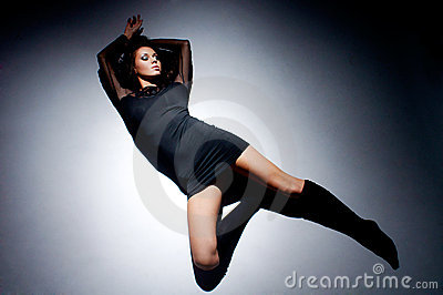 Beautiful woman lying on floor in light circle