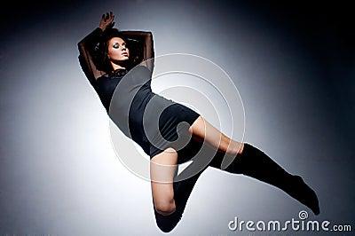 Beautiful woman lying on floor in light circle