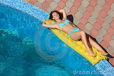Beautiful woman lying on an mattress near pool