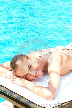 Beautiful woman lying on spa bed close to pool