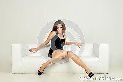 Beautiful woman lying on a white sofa,  on
