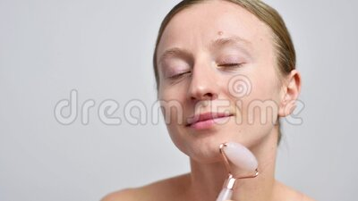 woman without makeup is getting massage face using jade