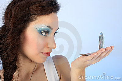 Beautiful woman with make-up looking at mirror