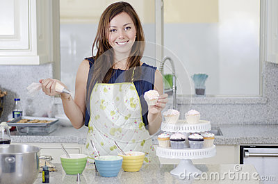 Beautiful woman making cupcakes