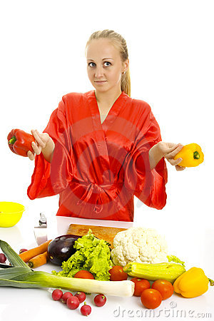 Beautiful woman making vegetable salad.