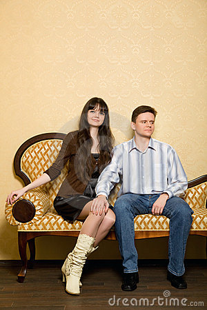 Beautiful woman and man sitting on sofa in room