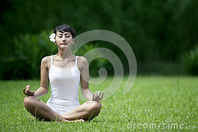 Beautiful Woman meditating in the garden