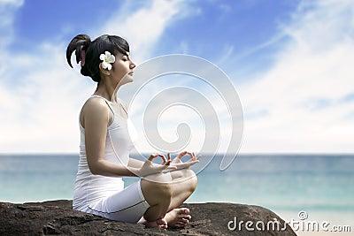 Beautiful woman meditating by the sea