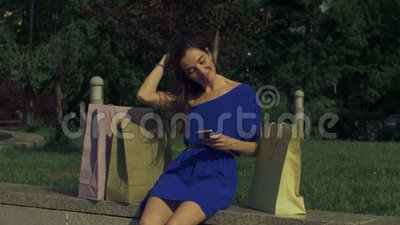 Carefree shopper woman using smart phone in the city stock video footage
