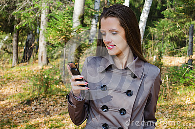 The beautiful woman with a mobile phone on walk in wood