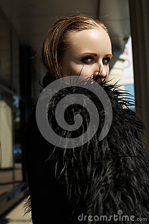 Beautiful woman model in fashion black warm jacket with fluffy fur