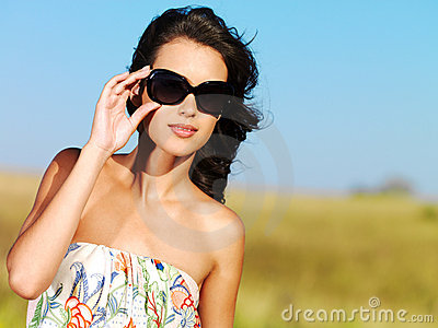 Beautiful woman on nature in black sunglasses