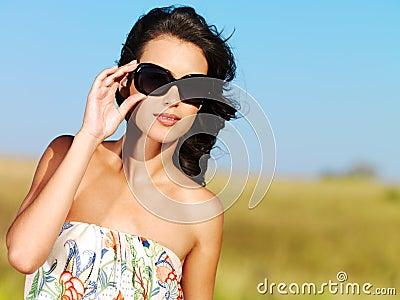 Beautiful woman on nature in black sunglasses