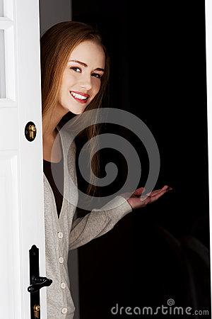 Beautiful woman is opening door and inviting to come in.