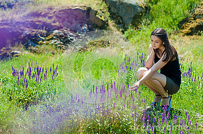 Beautiful woman outdoors & blooming flowers