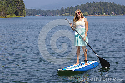 Beautiful woman paddleboarding on scenic lake