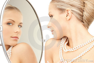 Beautiful woman with pearl beads and mirror