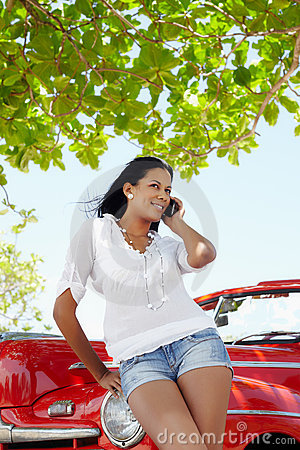 Beautiful woman on the phone near cabriolet car