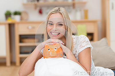 Beautiful woman with a piggy bank
