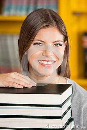 Beautiful Woman With Piled Books Smiling In