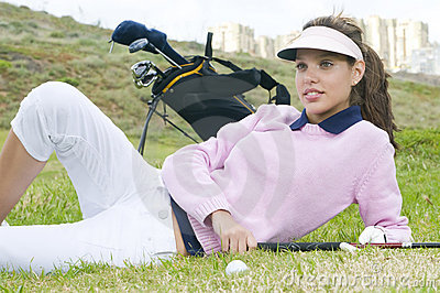 Beautiful woman player lying on the green