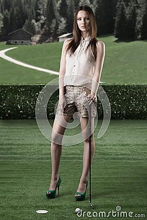 Beautiful woman plays golf with golf-club