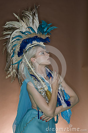 Beautiful woman posing in feathered outfit over colored background
