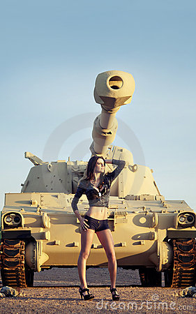 Beautiful woman posing beside tank