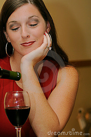 Beautiful woman pouring wine eyes closed