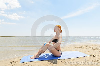 Beautiful woman practicing fitness by the sea