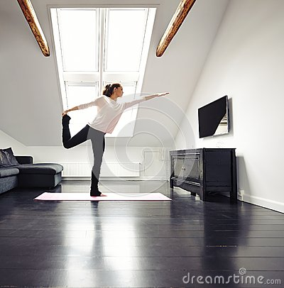 Beautiful woman practicing yoga exercises at home stock for Living room yoga timetable
