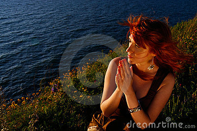 Beautiful woman praying by sea