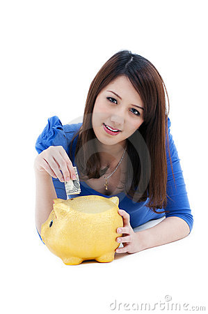 Beautiful woman putting money into piggy bank
