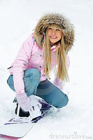 Beautiful woman putting on a snowboard