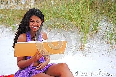 Beautiful woman reading on the beach