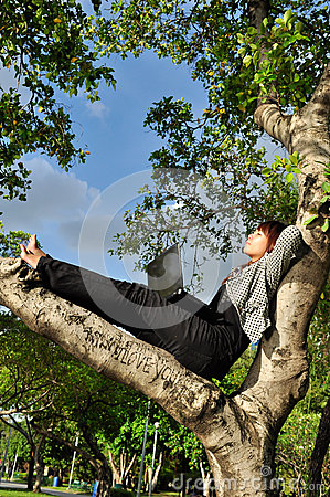 Beautiful woman resting on the tree with laptop