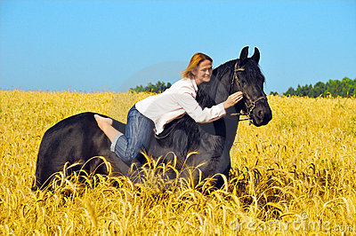 Beautiful woman rides and pets horse in field