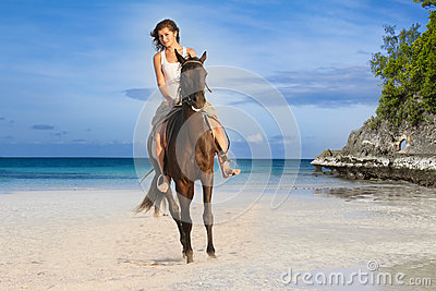 Beautiful woman riding a horse on tropical beach