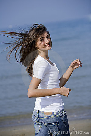 Beautiful woman running windblown on the beach