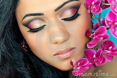 Beautiful woman s face with orchid flowers