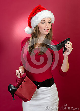 Beautiful woman with Santa Hat holding shoes