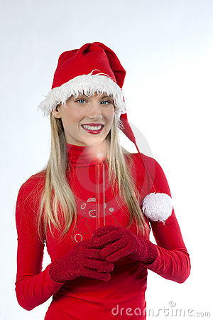 Beautiful woman in santa s hat holding a candle