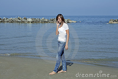 Beautiful woman by the seashore with a mobilephone