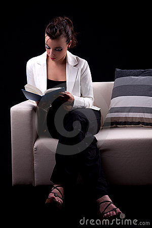Beautiful woman seated on couch reading a book