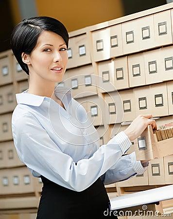 Beautiful woman seeks something in card catalog